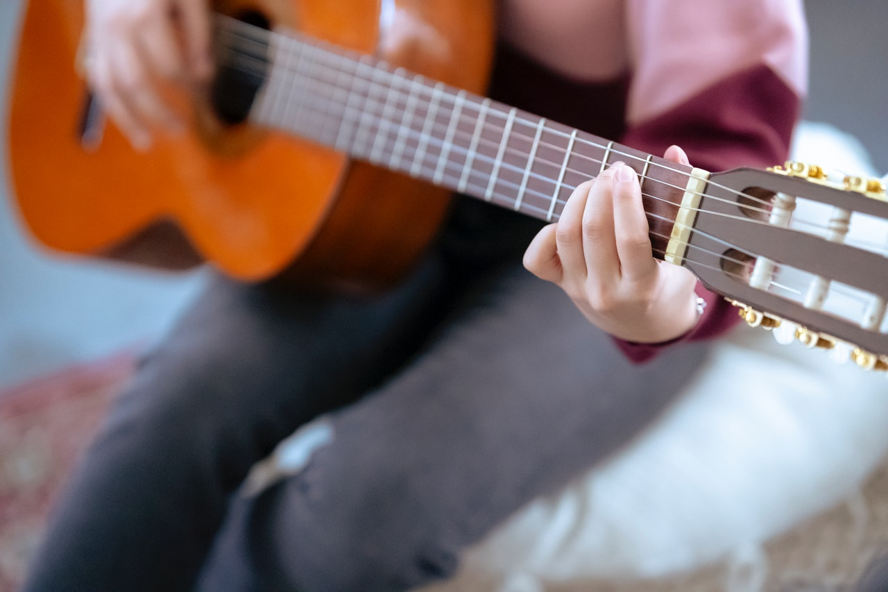 Person Sitting And Playing An Acoustic Guitar
